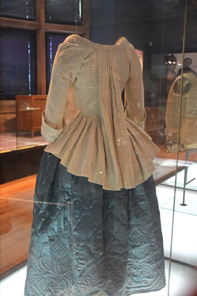 Petticoat, c1740, wadded quilted silk and wool, & jacket, 1781/1 cord quilted linen, Kelvingrove Museum, Glasgow, Scotland.  The wadded quilting in the petticoat includes a layer of light padding between the surface fabric and backing fabric. In the 1700s unwoven wool was used for the wadding. The peterlair or jacket is made of cord quilting, which involves stitching two layers of fabric together in a pattern worked in double parallel lines through which a narrow cord is threaded.  In the 1700s it was often used for summer daywear.
